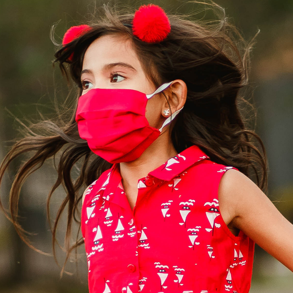 Photograph of a girl in motion. She is wearing a red dress and red mask, with red pom-poms in her brown hair.